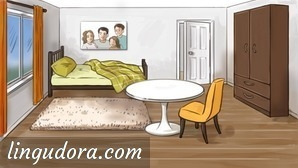 In the middle of a room there is a round table and a yellow chair beside it. The bed is in the back of the room. Above, on the wall, there is an image depicting a family. To the right of the bed a door is slightly opened. In front of the bed there is a carpet. Along the right wall there is a big brown wardrobe and on the opposite side a window with orange curtains is shown.